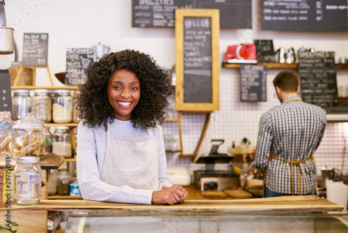 Fotografía Smiling young African American entrepreneur working behind her cafe counter