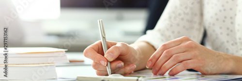 Obraz na plátne  Female hand holding silver pen working with financial document