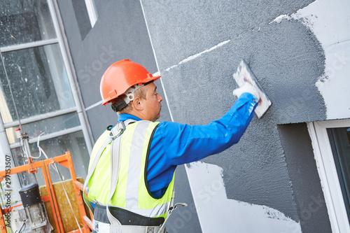 Fototapeta Facade worker plastering external wall of building obraz