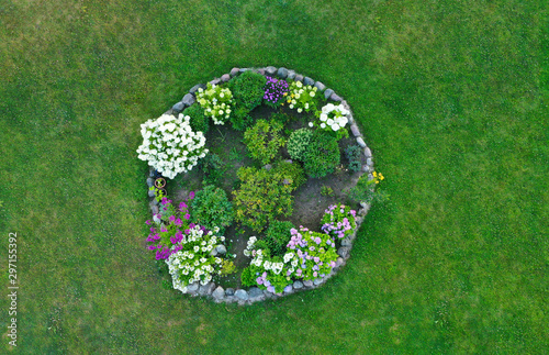 Canvas-taulu Aerial drone top down view on stylish round flowerbed surrounded by rock wall with violet, white and yellow blooming flowers
