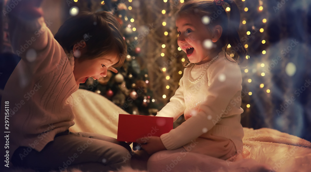 Fototapety, obrazy: Family on Christmas eve at fireplace. Kids opening Xmas presents. Children under Christmas tree with gift boxes. Decorated living room with traditional fire place. Cozy warm winter evening at home.