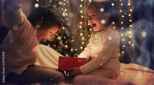 Fototapeta Family on Christmas eve at fireplace. Kids opening Xmas presents. Children under Christmas tree with gift boxes. Decorated living room with traditional fire place. Cozy warm winter evening at home. obraz