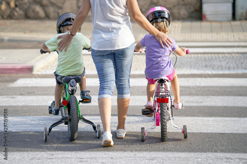 Fototapeta  Mother goes pedestrian crossing with children on bicycles