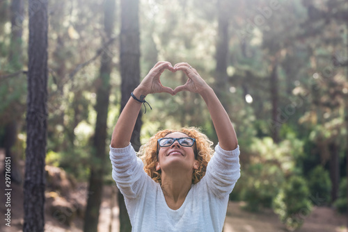 Respect outdoor nature and save the forests world concept with beautiful adult woman looking up and doing the hearth love sign wih her hands - forest and beautiful wood in background