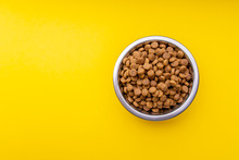 Dog Food In A Metal Bowl. Yellow Background