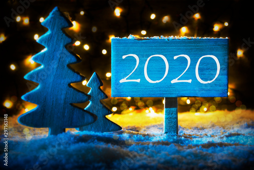 La pose en embrasure Nature Sign With Text 2020 For Happy New Year. Blue Christmas Tree With Snow And Magic Glowing Lights In Backround. Card For Seasons Greetings.