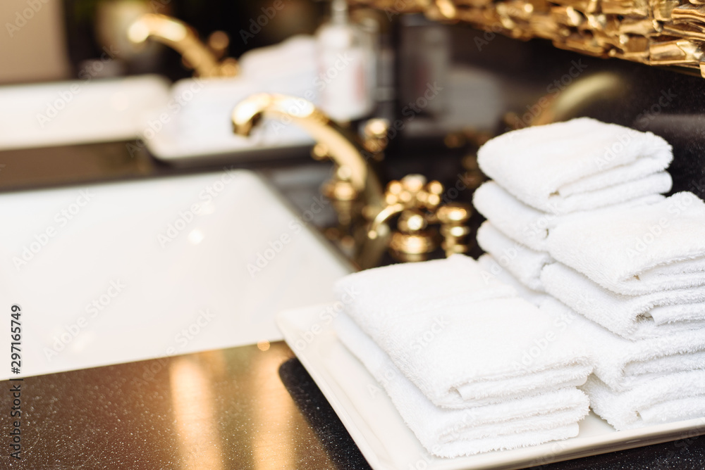 Fototapety, obrazy: A stack of fresh white towels in the hotel's luxurious bathroom. A gold faucet, mirror and marble sink in a public restroom of an expensive building