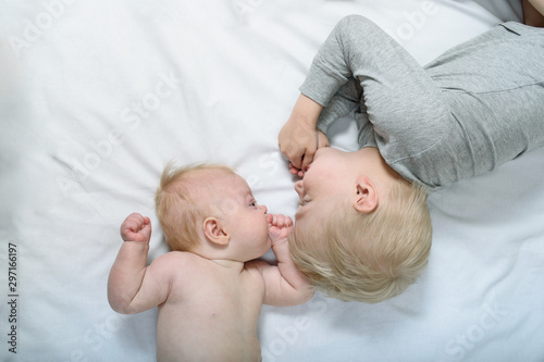 Fotografia, Obraz Baby and smiling older brother are lying on the bed