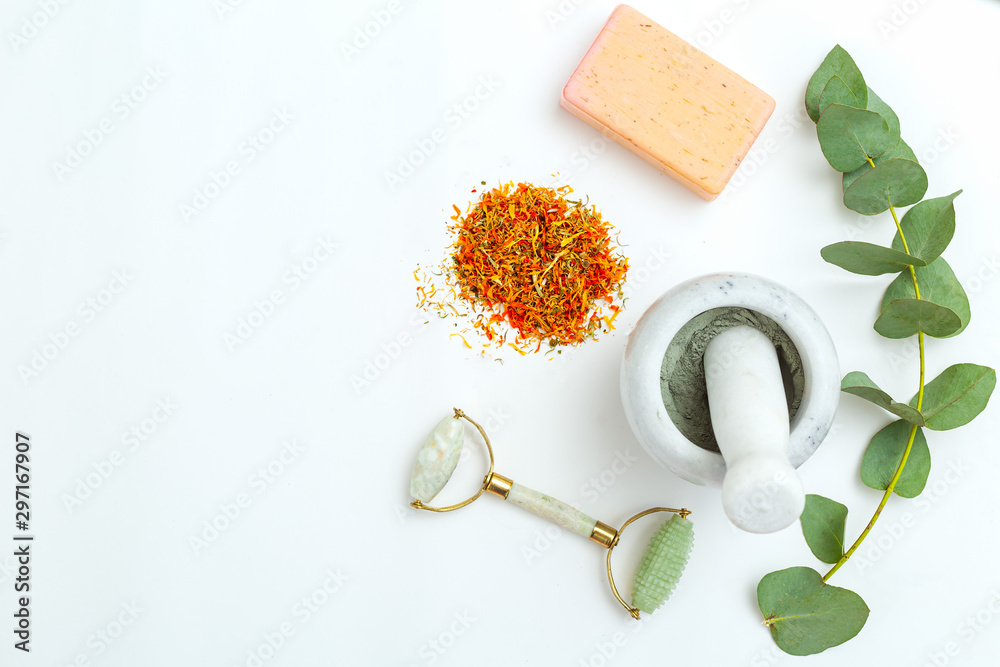 Fototapety, obrazy: Dried marigold flowers and face roller on white background. Apothecary. Natural skin care
