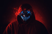 Man In Angry And Scary Lighting Neon Glow Mask In Hood On Dark Red Background. Halloween And Horror Concept