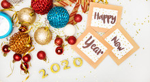 """A Good Wish. Close Up Of A Pile Of Multicolored Ornaments, A Blue Alarm Clock, Golden Confetti, Golden Numerals Of 2020 And Three Cardboard Frames With The Words """"Happy New Year"""" On Them."""