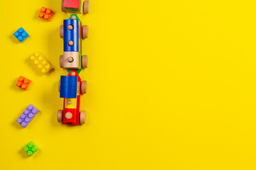 Toy background. Wooden toy train and colorful building brick blocks on yellow background