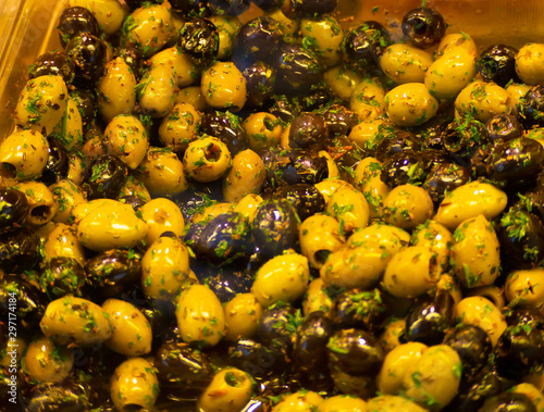 Fényképezés  Inlaid green and black olives with herbs and oil anitpasti from italian market s