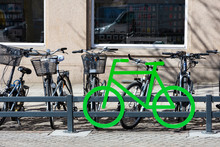 Bike Parking In The Center Of The City. Green Bike Symbol, City Bikes Parked In A Row Near Grey Building