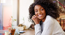 Young African American Woman Smiling While Sitting In A Cafe