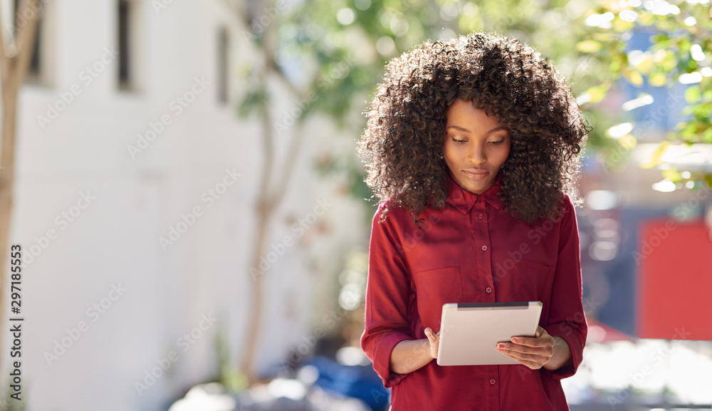 Fototapety, obrazy: Young African American woman using a tablet in the city