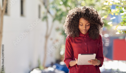 Pinturas sobre lienzo  Young African American woman using a tablet in the city