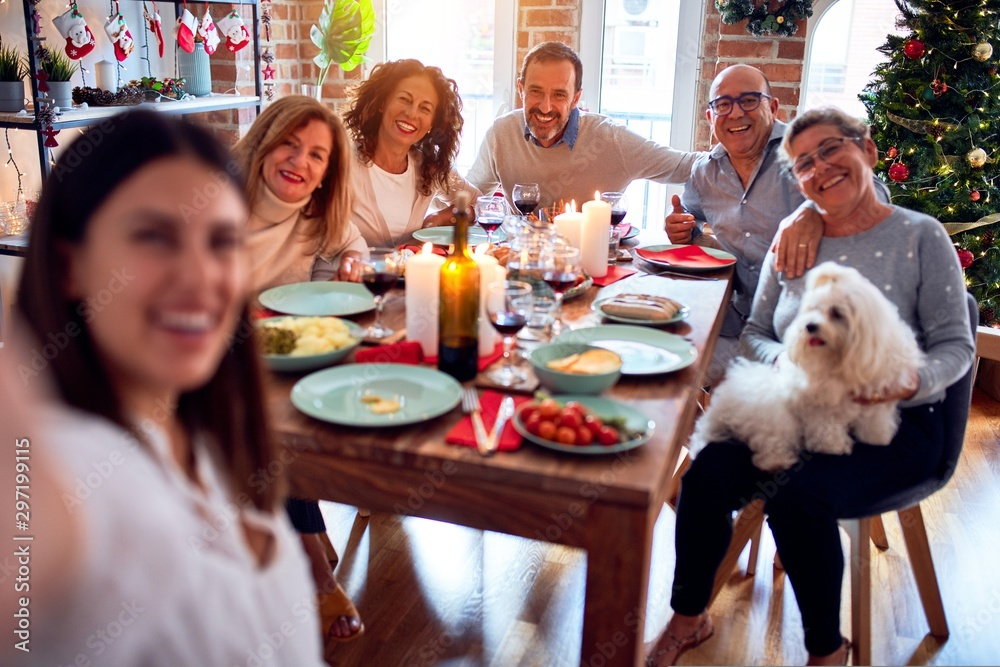 Fototapety, obrazy: Family and friends dining at home celebrating christmas eve with traditional food and decoration, taking a selfie picture together