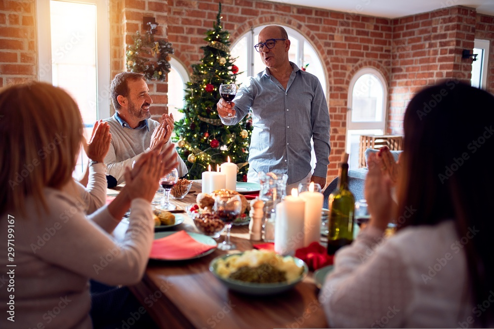 Fototapety, obrazy: Family and friends dining at home celebrating christmas eve with traditional food and decoration, making a toast for new year best wishes