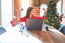 Beautiful Woman Sitting At The Table Working With Laptop At Home Around Christmas Tree Showing Arms Muscles Smiling Proud. Fitness Concept.