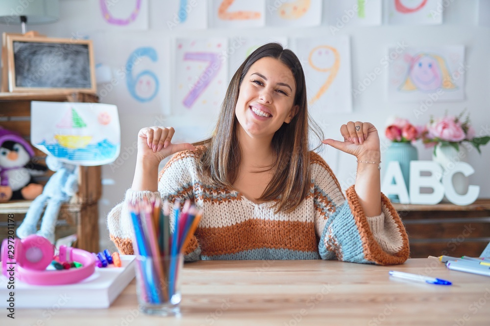 Fototapety, obrazy: Young beautiful teacher woman wearing sweater and glasses sitting on desk at kindergarten looking confident with smile on face, pointing oneself with fingers proud and happy.