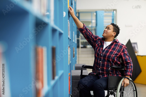Valokuvatapetti Portrait of disabled student in wheelchair choosing books while studying in coll