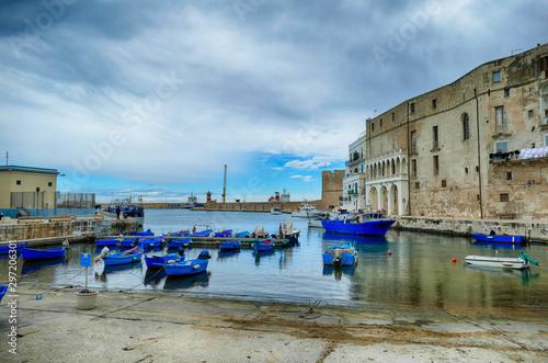 Small boats in the marina harbor of Polignano