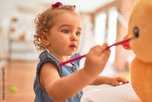 Fotografiet Beautiful caucasian infant playing with toys at colorful playroom