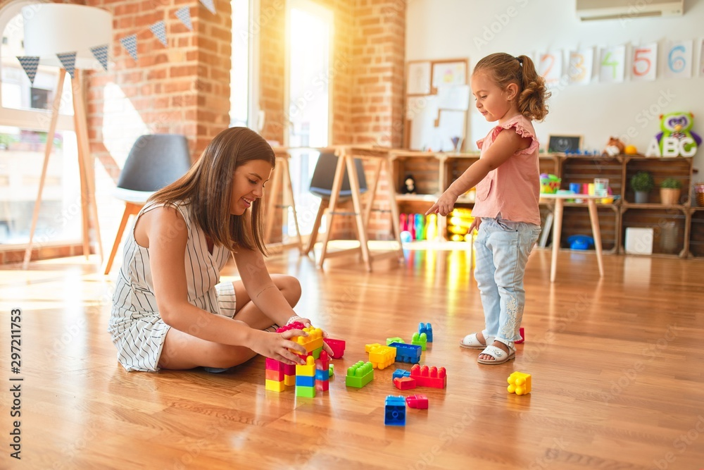 Fototapety, obrazy: Beautiful teacher and blond toddler girl building tower using plastic blocks at kindergarten