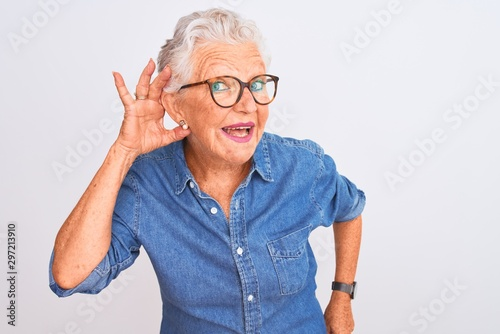 Senior grey-haired woman wearing denim shirt and glasses over isolated white background smiling with hand over ear listening an hearing to rumor or gossip Fototapete