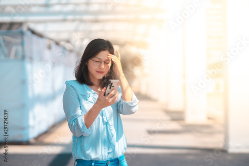 Photo Young woman using smartphone under   harsh sun light