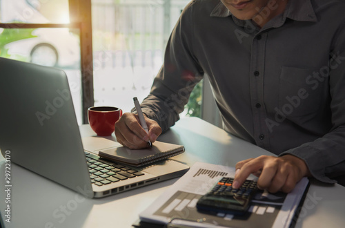 Male businessman use the calculator and take notes with calculations about the expenses at the office. Prepare to submit annual tax.