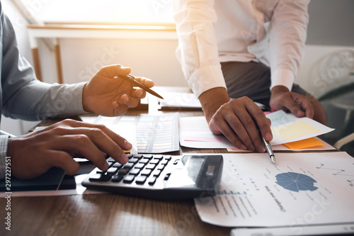 Managers using calculator to analyze sales cost reports and explain summary reports to employees calculate and record summary information data in the office Wallpaper Mural