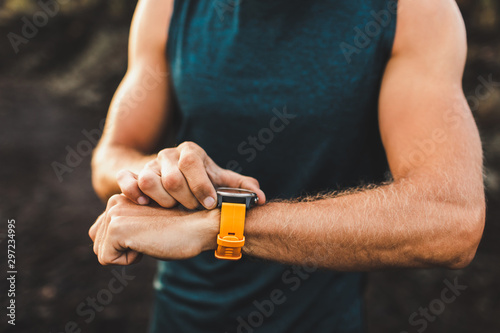 Canvastavla  Young athletic man using fitness tracker or smart watch before run training outdoors