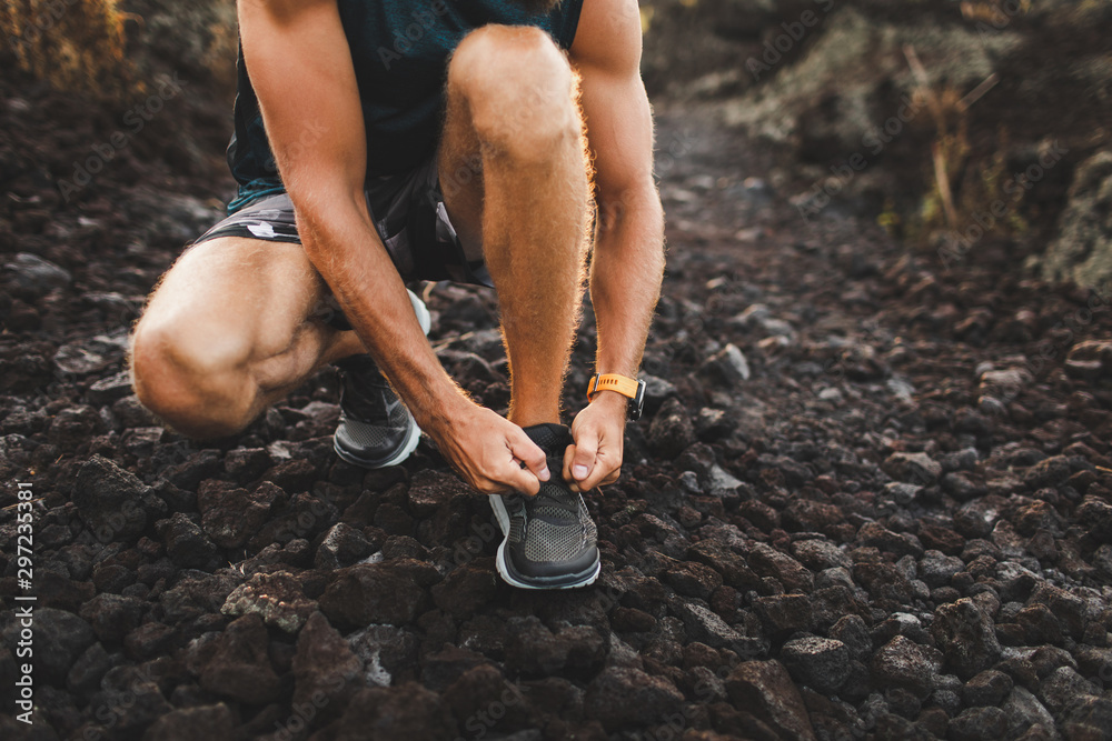 Fototapety, obrazy: Man tying running shoes before trail running outdoors. Close-up