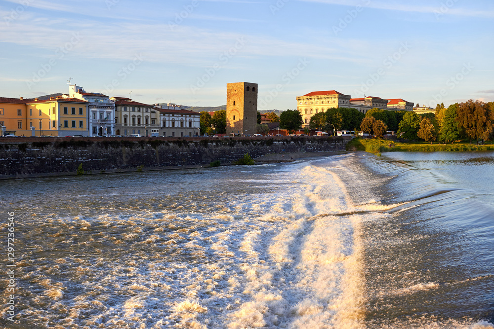 Fototapeta Arno River with waterfall and old city buildings at sunset, Florence, Italy