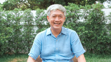 Portrait Asian Chinese Senior Man Feeling Happy Smiling At Home. Older Male Relax Toothy Smile Looking To Camera While Lying In The Garden At Home In The Morning Concept.