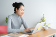 Young asian woman working on laptop in the home office desk, And sit at table resting chin on hand.