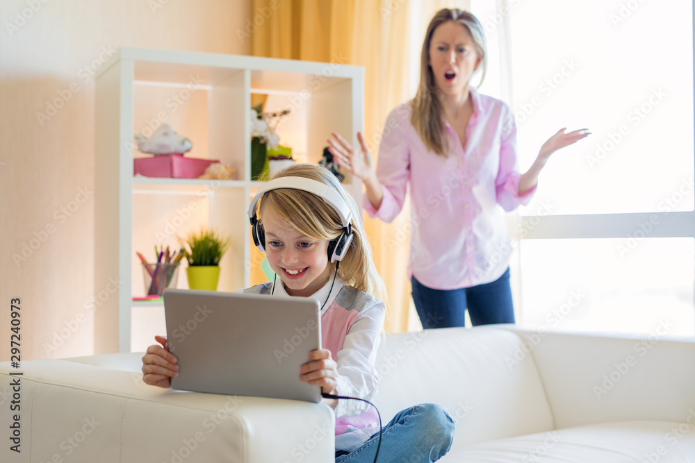 Fototapety, obrazy: Woman is scolding her teenage daughter, girl is listening to music in headphones and ignoring her mom