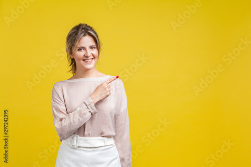 Photo Look attention, advertise here! Portrait of joyous beautiful woman with fair hair in casual blouse standing, pointing aside and looking at camera