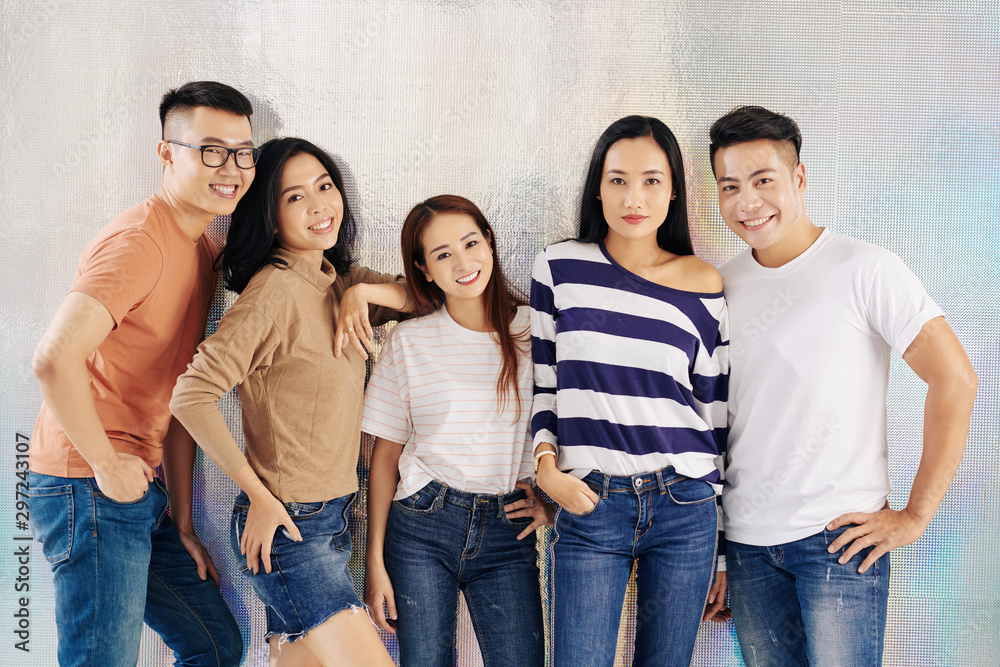 Fototapeta Beautiful smiling young Vietnamese models posing together against holographic background