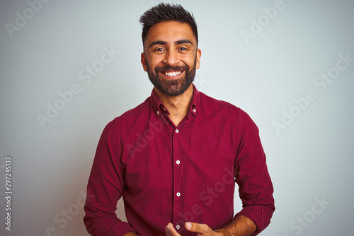 Obraz na plátně Young indian man wearing red elegant shirt standing over isolated grey background with hands together and crossed fingers smiling relaxed and cheerful