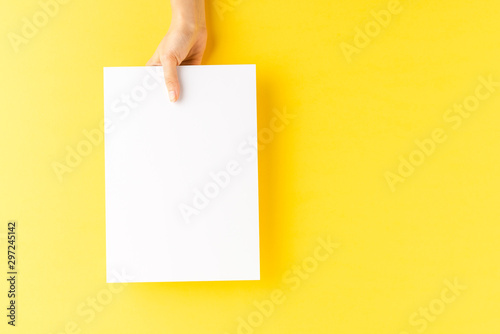 Fotografering  Young woman's hand showing blank paper sheet on yellow desktop