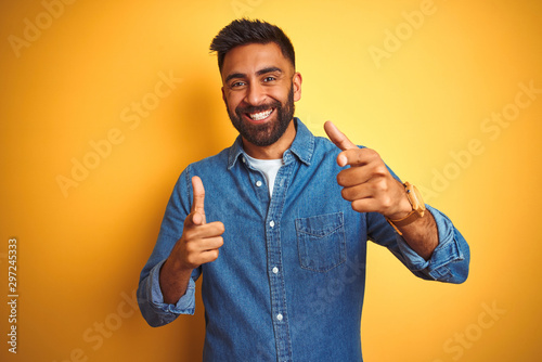 Young indian man wearing denim shirt standing over isolated yellow background pointing fingers to camera with happy and funny face. Good energy and vibes.