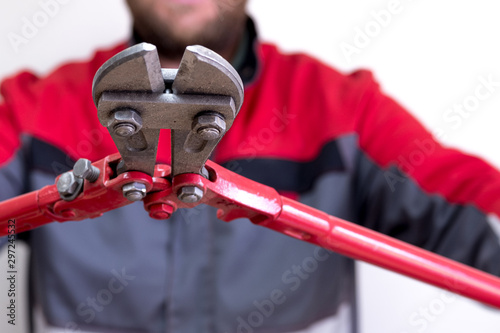 Fototapeta man in working clothes holding in both hands a large pair of scissors for cutting the rods of the scissors is aimed at the camera obraz
