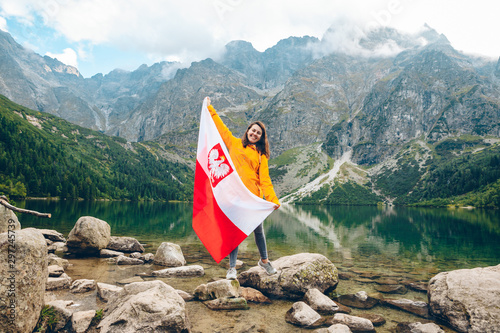young pretty smiling woman holding poland flag at beach of mountain lake