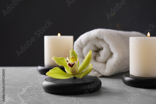 Stampa su Tela  Spa stones with exotic flower and burning candles on grey table against dark bac