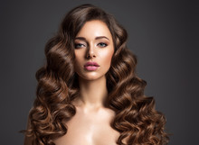 Beautiful Woman With Long Brown Hair. Beautiful Face Of An Attractive Model With Natural Makeup. Beauty  Of Curly Hair. Closeup Portrait  Of Caucasian Stunning Girl.