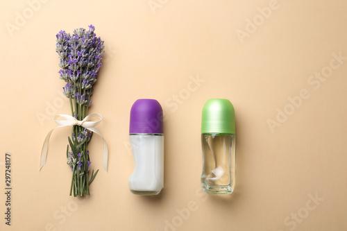 Female deodorants and lavender flowers on beige background, flat lay Wallpaper Mural