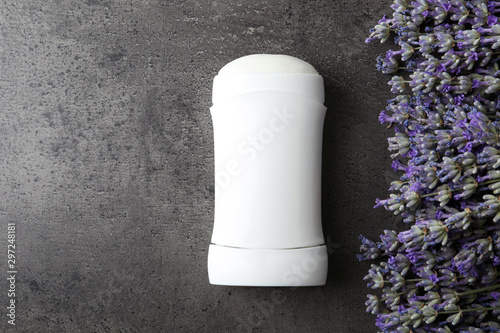 Female deodorant and lavender flowers on grey stone background, flat lay Wallpaper Mural
